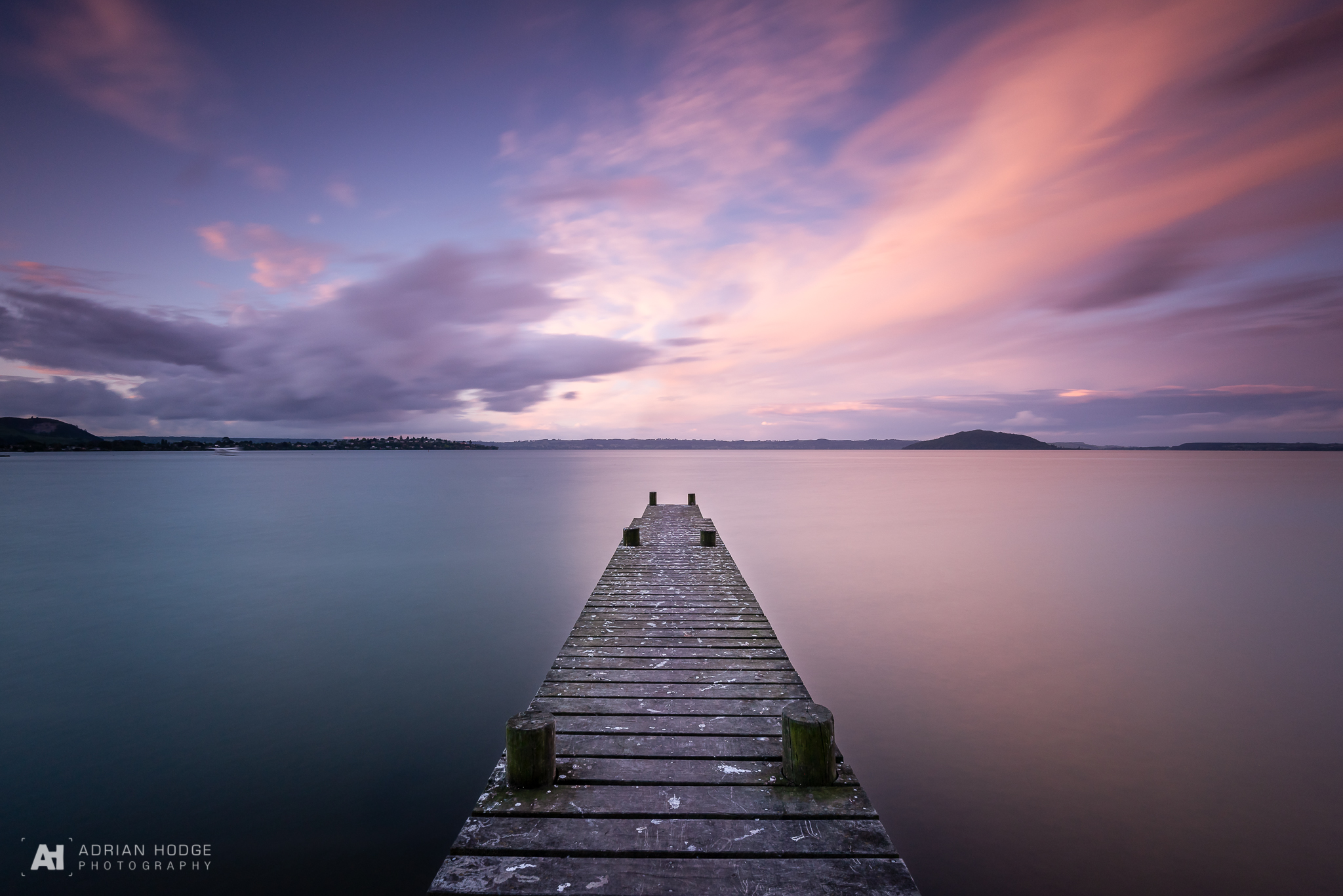A long exposure of a jetty pointing straight out into a lake with a colourful pink sky at sunset.