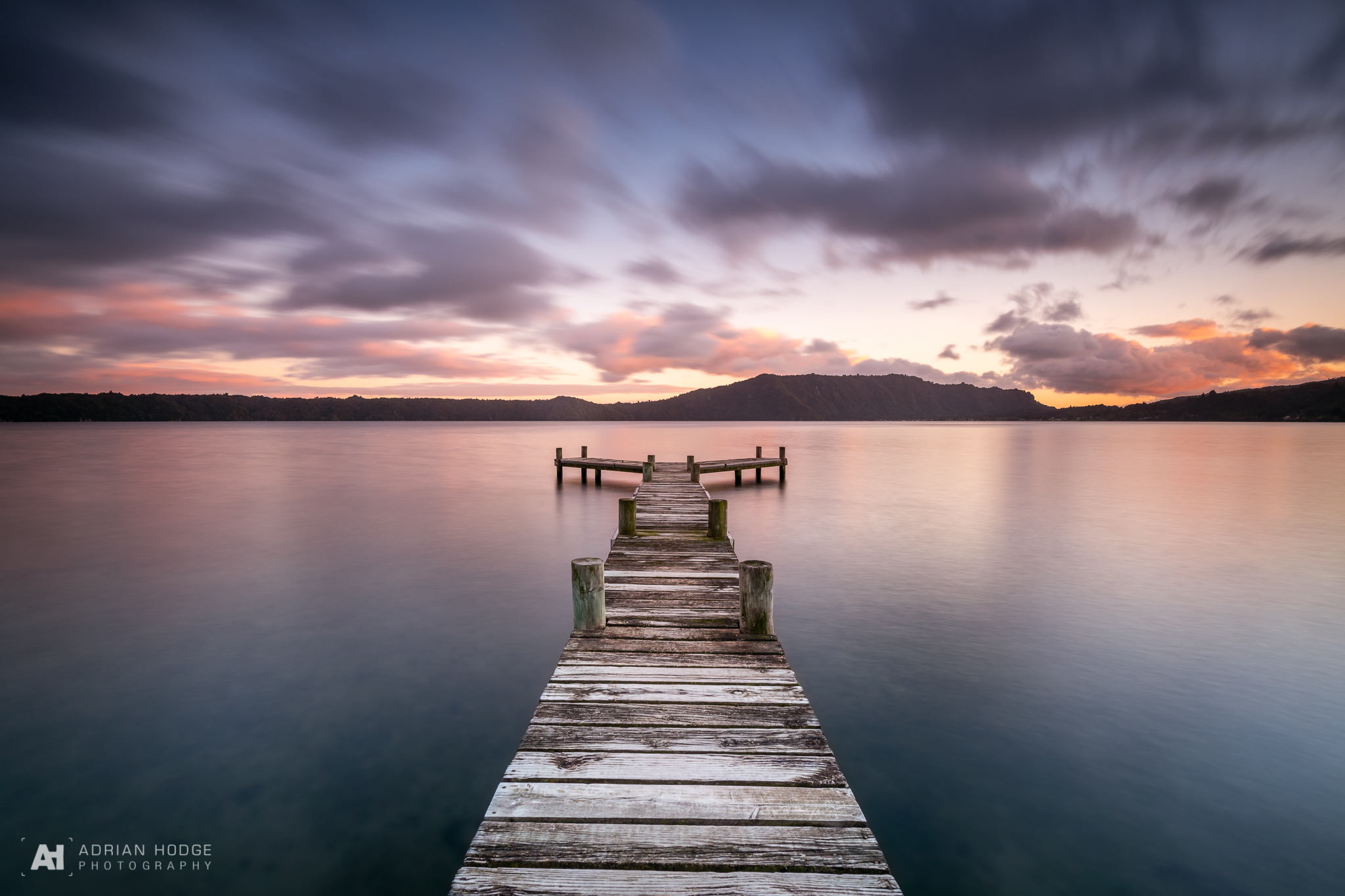 A long exposure of a jetty pointing straight out into a lake with a colourful pink sky at sunrise.